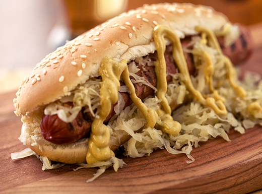 A hot dog rests on its side in a seeded bun covered with yellow mustard and sauerkraut on a wooden plate at Biker Jim's in Denver, Colorado.