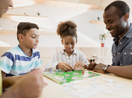 A father smiles as he plays a green board game on a white tabletop with his daughter and son while on a family trip in Denver, Colorado.