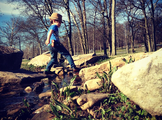 A child stepping over rocks in a creek in Shelby Park on a crisp morning with bare trees in the background.