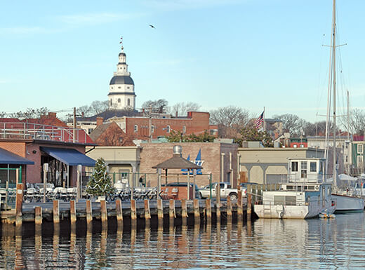 A view of the harbor with docked boats and nearby skyline of Annapolis, Maryland on an early spring evening.