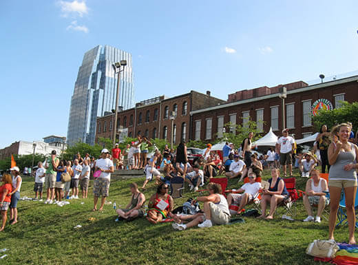 A crowd of people mingle and sit on grass on a hill at Riverfront Park in Nashville, Tennessee to listen to a free live music on a sunny day.