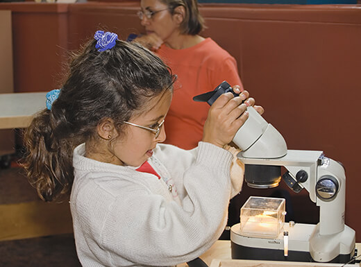 A young girl dressed in a white lab coat playing with a lighted microscope at the Washington D.C Smithsonian.