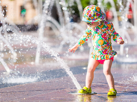 A toddler dressed in a colorful bathing suit and matching hat steps on an in-ground water fountain in Denver, Colorado on a hot summer afternoon.