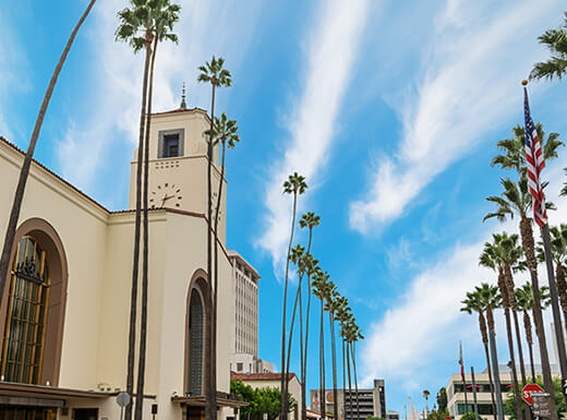 Los Angeles' historic Union Station combines Art Deco, Mission Revival, and Streamline Moderne architecture among tall palm trees and a blue sky with wispy white clouds on a sunny day.