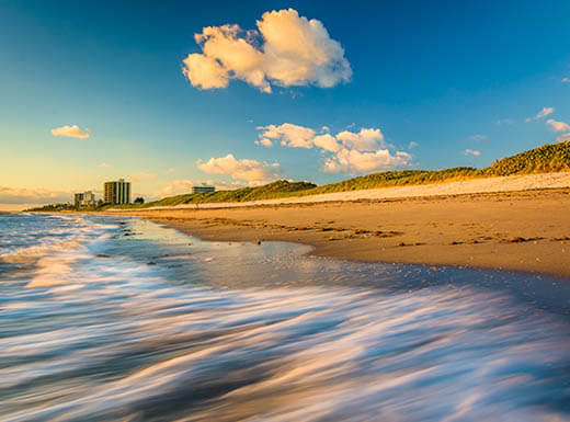 Waves rolling onto the beach at Coral Cove Park on Jupiter Island in West Palm Beach at sunrise shows white puffy clouds in the blue sky and the yellow sunlight reflecting off of the water and the sandy shore.