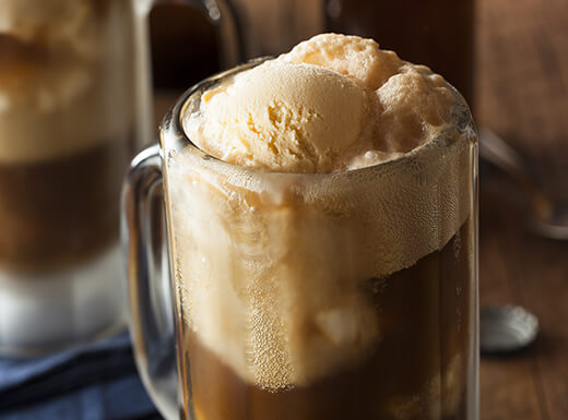 Scoops of vanilla ice cream floats on top of a root beer float in a frosted mug.