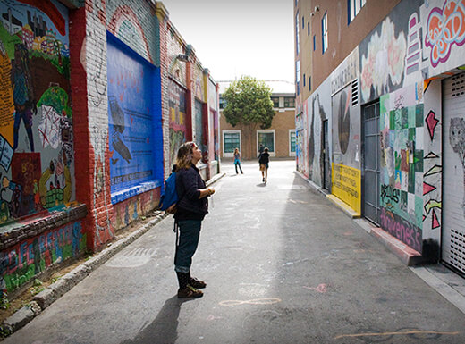 Tourist admires wall art in an brightly lit roadway alley in San Francisco.