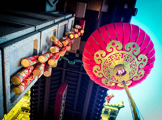 a red and gold lantern is pictured from below at the Chinatown gate on a clear afternoon in San Francisco, California