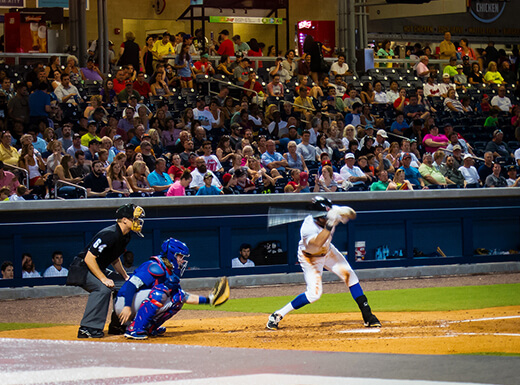 An action photo of the Nashville Sounds baseball team playing at First Tennessee Park with fans in the stadium seats in the background.