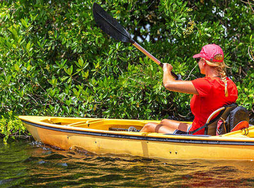 A girl kayaking in Everglades National Park, Florida, wears a red shirt in a yellow kayak with bright green foliage in the background.