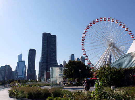 View of the red and white Centnnial Ferris wheel and cityscape at Chicago's Navy Pier on a clear summer morning.
