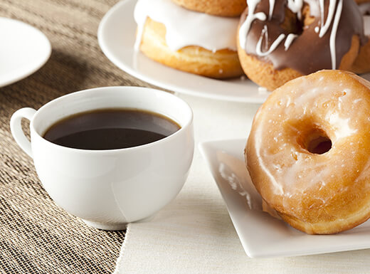 Black coffee in a white mug sits beside a glazed donut on top of white napkins.