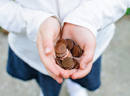A girl wearing a white shirt and blue skirt holds a pile of pennies in her hands at the Denver Mint on an overcast afternoon in Denver, Colorado.