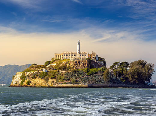 Alcatraz Island is pictured in the middle of San Francisco Bay in San Francisco, California on sunny day, showing the prison and buildings surrounded by overgrown greenery on the island