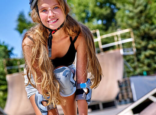 Alt= A teenage girl with long flowing hair rides a skateboard at the Denver Skate Park while wearing a helmet, elbow, knee, and wrist pads on a clear spring afternoon in Denver, Colorado.