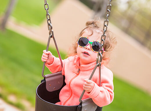 A toddler with curly hair wearing sunglasses and a pink jacket rides in a bucket swing at a grassy playground in Denver, Colorado on a summer morning.