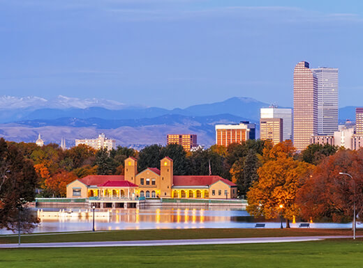 A white stone boathouse is illuminated on a lake in Denver's City Park, with the Denver skyline and the Rocky Mountains in the background early on an autumn morning.