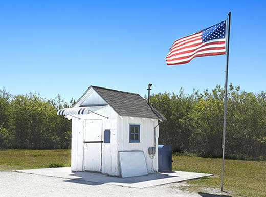 A view of the smallest post office in the U.S., in Ochopee, Florida, a small wooden, white building next to American flag waving in the breeze on a sunny day.