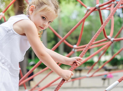 A young girl in a white dress climbs on a rope structure at an urban playground in Denver, Colorado on a warm day.