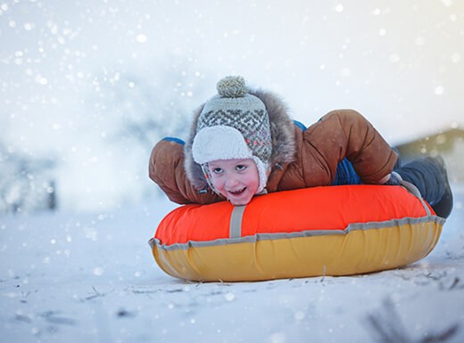 A boy wearing a gray hat and brown jacket slides on his stomach on a yellow and orange tube along the snow in Denver on a cold winter day.
