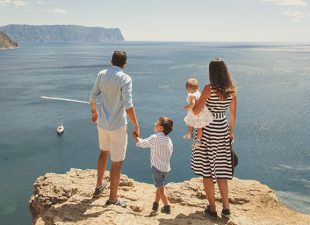 A family of four stands on a plateau overlooking the ocean on a beautiful summer day.