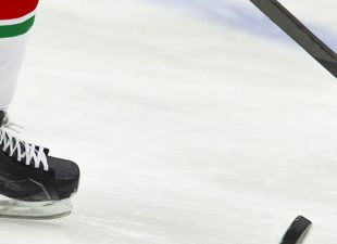 A hockey player skates down the ice.