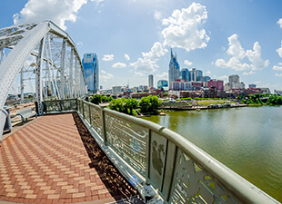 = A view of downtown Nashville, Tennessee from a bridge over the Cumberland River on a sunny day.