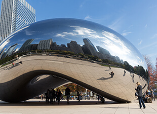Cloud Gate, also known as The Bean, in a Chicago park with tourists taking photos of the piece's reflection of the city