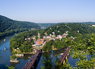 An aerial panoramic view of Harpers Ferry, found at the confluence of the Potomac and Shenandoah Rivers from Maryland Heights on a clear afternoon.