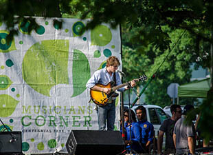 A man plays guitar on stage during a free concert at Nashville's Musician's Corner, Centennial Park on an early evening.