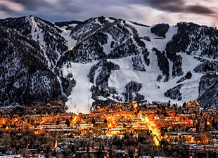 Aerial view of Aspen, Colorado, and the city lights at dusk with snow-covered mountains in the background.
