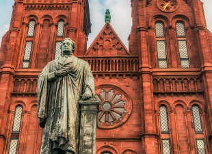 Washington D.C.'s red stone Smithsonian castle house and stone statue on an cloudy afternoon.