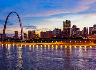 The Eads Bridge over the Mississippi River with the St. Louis city skyline illuminated as the sun sets.