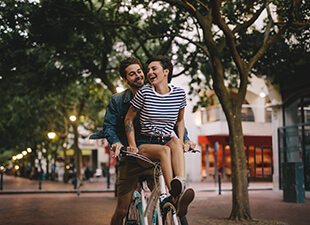 Couple riding a bike together.