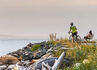 A cyclist wearing a bright green jersey overlooking an ocean cliff during a morning sunrise.