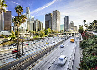 City skyline of Los Angeles, California over a busy highway lined with palm trees on a bright afternoon.