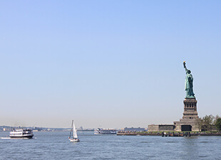 Distant view of the Statue of Liberty on a sunny day from the Hudson River near lower Manhattan with sailboats and ferries nearby.