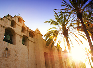 Mission San Gabriel Arcangel, a building and now museum constructed of adobe, stands with palm trees and the sun beaming behind it in Los Angeles during a golden sunrise.