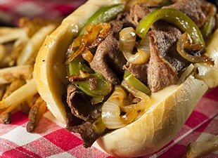 A Philly cheesesteak with grilled beef, onions and green peppers sits open on a toasted white bun with French fries beside it on a red and white checkered table cloth.