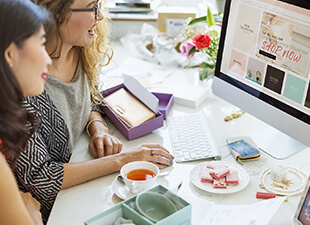 Two female friends sit at a desk with tea and snacks as they browse online shopping sites on a bright afternoon.