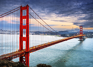 View of the Golden Gate Bridge in San Francisco, California, on a cloudy afternoon with turquoise water under the bridge.
