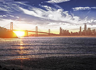 Panorama of downtown San Francisco, California and the Bay Bridge at sunset shows the sun behind the skyline from across the water on a clear evening.