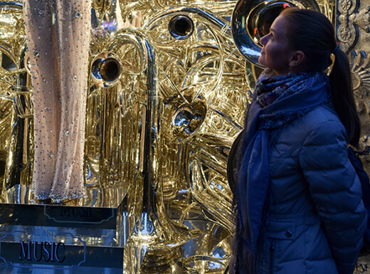 A young girl looking at a gold-colored holiday window display in New York City on a bustling evening.
