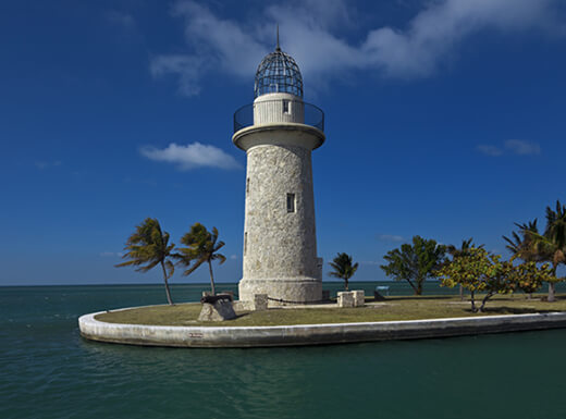 A stone lighthouse on Boca Chita Key near the water by picturesque palm trees, in Biscayne National Park, Florida, under a blue sky.