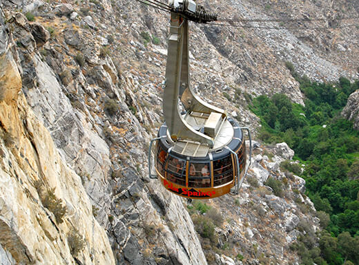 Palm springs aerial tram is pictured as it glides over rocky terrain, just a short day trip from Palm Springs, California.
