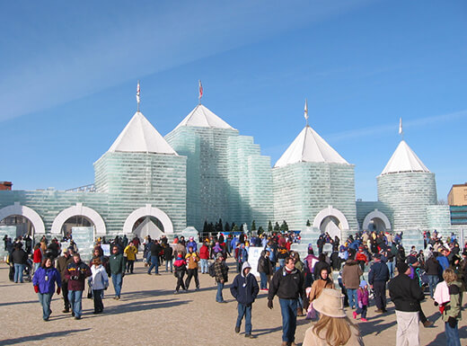 Groups of visitors at the Saint Paul Winter Carnival Ice Castle in Minnesota on a clear day.