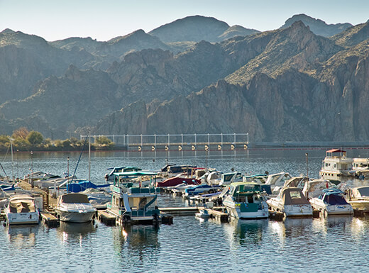 Boats docked at Saguaro Lake Marina near Phoenix, Arizona, with the Goldfield Mountains in the background on a sunny, clear day.