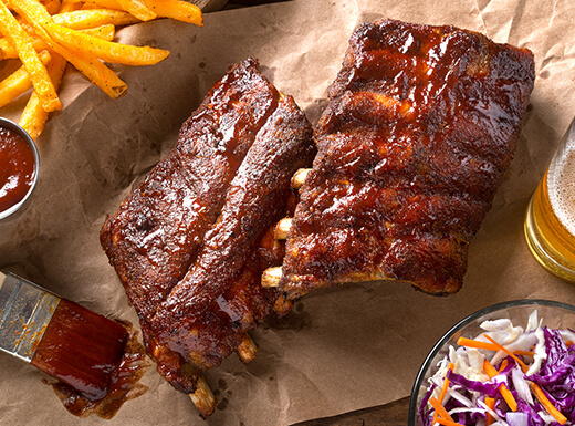 alt= An up-close shot of freshly grilled BBQ ribs with coleslaw and fries on the side.