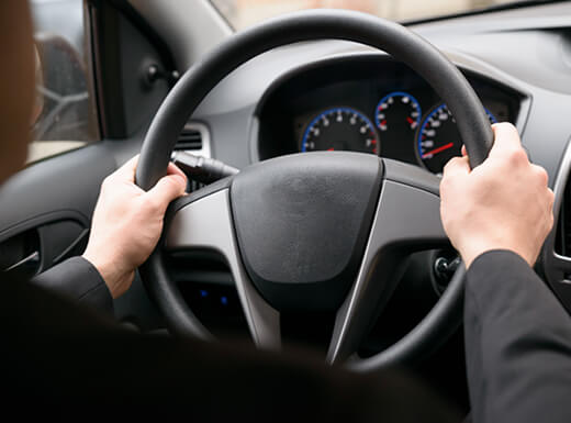 A driver wearing black long sleeves holds a black steering wheel with both hands at the 9 and 3 o'clock position with the dashboard in the background.