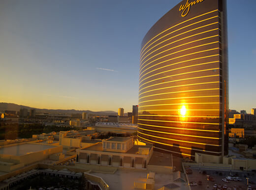 The sunrise is reflected off the side of the Wynn Las Vegas hotel in Las Vegas, Nevada on an early morning.